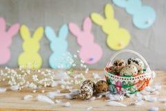 Состав пасхи яичек триперсток пасхи в корзине и с гирляндой зайчика на деревянной предпосылке Стоковые Изображения RF