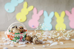 Состав пасхи яичек триперсток пасхи в корзине и с гирляндой зайчика на деревянной предпосылке Стоковая Фотография