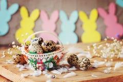 Состав пасхи яичек триперсток пасхи в корзине и с гирляндой зайчика на деревянной предпосылке Стоковое Изображение RF