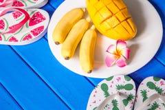 Состав плодоовощей манго банана на голубой деревянной предпосылке Стоковые Фото