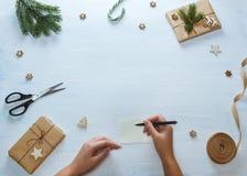 Состав подарка рождества упаковывая Женские руки с ручкой, подарки рождества, конфета, ель разветвляют, ножницы, лента, дальше Стоковая Фотография