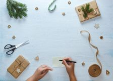 Состав подарка рождества упаковывая Женские руки с ручкой, подарки рождества, конфета, ель разветвляют, ножницы, лента, дальше Стоковые Фото