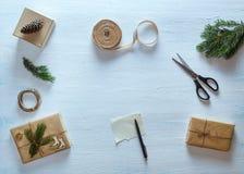 Состав подарка рождества упаковывая Подарки рождества, ель разветвляют, ножницы, лента, ручка с чистым листом на голубом столе Стоковое Изображение