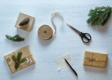 Состав подарка рождества упаковывая Подарки рождества, ель разветвляют, ножницы, лента, ручка с чистым листом на голубом столе Стоковая Фотография RF