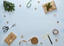 Состав подарка рождества упаковывая Подарки рождества, конфета, ель разветвляют, ножницы, лента, ручка с чистым листом дальше Стоковая Фотография RF