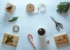 Состав подарка рождества упаковывая Подарки рождества, чашка чаю, конфета, ель разветвляют, ножницы, лента Плоское положение, вер Стоковые Фото