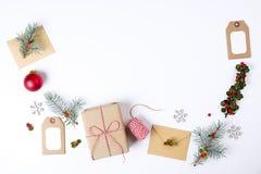 Состав рамки рождества Подарок рождества, ветвь сосны, красные шарики, конверт, белые деревянные снежинки, лента и красные ягоды  Стоковые Фотографии RF