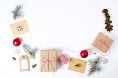 Состав рамки рождества Подарок рождества, ветвь сосны, красные шарики, конверт, белые деревянные снежинки, лента и красные ягоды  Стоковое Изображение