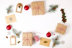 Состав рамки рождества Подарок рождества, ветвь сосны, красные шарики, конверт, белые деревянные снежинки, лента и красные ягоды  Стоковые Фото