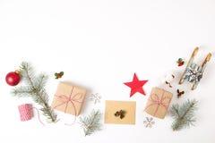 Состав рамки рождества Подарок рождества, ветвь сосны, красные шарики, конверт, белые деревянные снежинки, лента и красные ягоды  Стоковые Изображения RF
