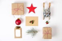 Состав рамки рождества Подарок рождества, ветвь сосны, красные шарики, конверт, белые деревянные снежинки, лента и красные ягоды  Стоковые Изображения