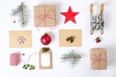 Состав рамки рождества Подарок рождества, ветвь сосны, красные шарики, конверт, белые деревянные снежинки, лента и красные ягоды  Стоковое Фото