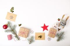 Состав рамки рождества Подарок рождества, ветвь сосны, красные шарики, конверт, белые деревянные снежинки, лента и красные ягоды  Стоковое фото RF