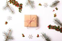 Состав рамки рождества Подарок рождества, ветвь сосны, красные шарики, конверт, белые деревянные снежинки, лента и красные ягоды  Стоковое Изображение RF