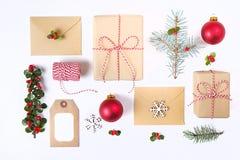 Состав рамки рождества Подарок рождества, ветвь сосны, красные шарики, конверт, белые деревянные снежинки, лента и красные ягоды  Стоковая Фотография RF
