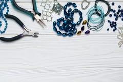 Состав ремесла заключений ювелирных изделий handmade с приукрашиваниями шариков плоскогубцев на белой деревянной предпосылке стоковое изображение rf