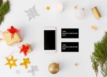 Состав рождества визитных карточек Smartphone ветви ели, конусы и украшения рождества на белой предпосылке Стоковые Изображения