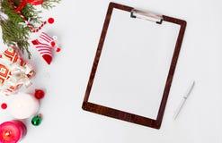 Состав рождества доски сзажимом для бумаги ветви ели, конусы и украшения рождества на белой предпосылке Плоское взгляд сверху пол Стоковые Изображения
