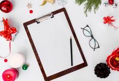 Состав рождества доски сзажимом для бумаги ветви ели, конусы и украшения рождества на белой предпосылке Плоское взгляд сверху пол Стоковые Изображения RF