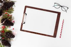 Состав рождества доски сзажимом для бумаги ветви ели, конусы и украшения рождества на белой предпосылке Плоское взгляд сверху пол Стоковая Фотография RF