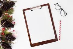 Состав рождества доски сзажимом для бумаги ветви ели, конусы и украшения рождества на белой предпосылке Плоское взгляд сверху пол Стоковое Фото