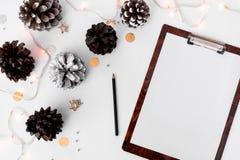 Состав рождества доски сзажимом для бумаги для клеймить конусы и украшения рождества на белой предпосылке Плоское взгляд сверху п Стоковое Фото