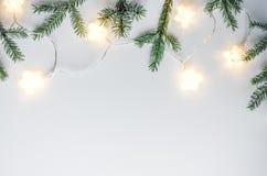 Состав рождества мягкий и уютный Ветви ели, handmade звезды и электрические лампочки на белой предпосылке Стоковая Фотография RF