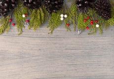 Состав рождества на время рождества Конусы сосны, ветви ели и украшения рождества на деревянной предпосылке Стоковое Фото