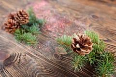 Состав рождества от ветвей спруса и конусов на посватать стоковые фото