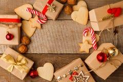 Состав рождества различных подарочных коробок в лентах золота ремесла и печеньях пряника сладости праздника украшенных бумагой кр стоковое фото