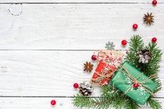Состав рождества сделанный ветвей ели, красных ягод, подарочных коробок и конусов сосны стоковые изображения rf