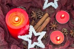 Состав рождества с с красными свечами, украшениями звезды, специями зимы и конусами Стоковая Фотография