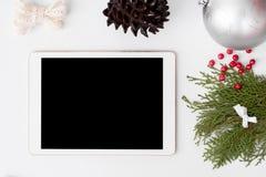 Состав рождества таблетки ветви ели, конусы и украшения рождества на белой предпосылке Плоское взгляд сверху положения Стоковая Фотография