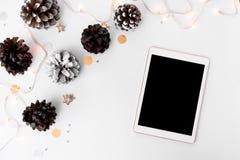 Состав рождества таблетки на время рождества конусы и украшения рождества на белой предпосылке Стоковое фото RF