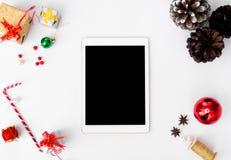 Состав рождества таблетки на время рождества конусы и украшения рождества на белой предпосылке Стоковые Фотографии RF