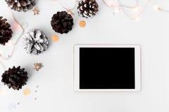 Состав рождества таблетки на время рождества конусы и украшения рождества на белой предпосылке Стоковое Фото