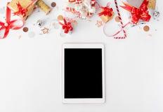 Состав рождества таблетки Подарки и украшения рождества на белой предпосылке Плоское взгляд сверху положения Стоковые Фотографии RF