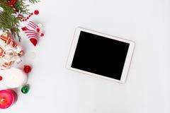 Состав рождества таблетки Подарки и украшения рождества на белой предпосылке Плоское взгляд сверху положения Стоковое фото RF