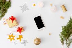 Состав рождества Smartphone ветви ели и украшения рождества на белой предпосылке Стоковые Изображения