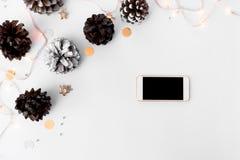 Состав рождества Smartphone ветви ели, конусы и украшения рождества на белой предпосылке Стоковые Изображения RF