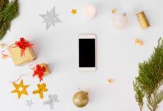 Состав рождества Smartphone Подарки и украшения рождества на белой предпосылке Плоское взгляд сверху положения Стоковые Фотографии RF