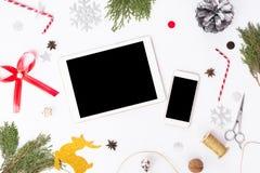 Состав рождества smartphone таблетки ветви ели, конусы и украшения рождества на белой предпосылке Плоское взгляд сверху положения Стоковая Фотография RF