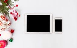 Состав рождества smartphone таблетки ветви ели, конусы и украшения рождества на белой предпосылке Плоское взгляд сверху положения Стоковые Изображения