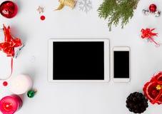 Состав рождества smartphone таблетки ветви ели, конусы и украшения рождества на белой предпосылке Плоское взгляд сверху положения Стоковая Фотография