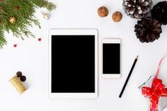 Состав рождества smartphone таблетки ветви ели, конусы и украшения рождества на белой предпосылке Плоское взгляд сверху положения Стоковые Изображения RF