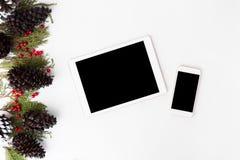 Состав рождества smartphone таблетки ветви ели, конусы и украшения рождества на белой предпосылке Плоское взгляд сверху положения Стоковые Фотографии RF