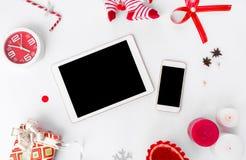 Состав рождества smartphone таблетки конусы и украшения рождества на белой предпосылке Плоское взгляд сверху положения Стоковое Изображение RF