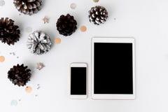 Состав рождества smartphone таблетки на время рождества конусы и украшения рождества на белой предпосылке Стоковое Изображение