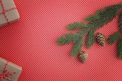 Состав рождества с подарками Xmas, ветвью ели и предпосылкой красного цвета конуса сосны Взгляд сверху, плоское положение Скопиру Стоковые Фотографии RF