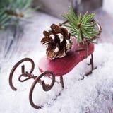 Состав рождества с санями, pinecone и украшением Стоковое Фото